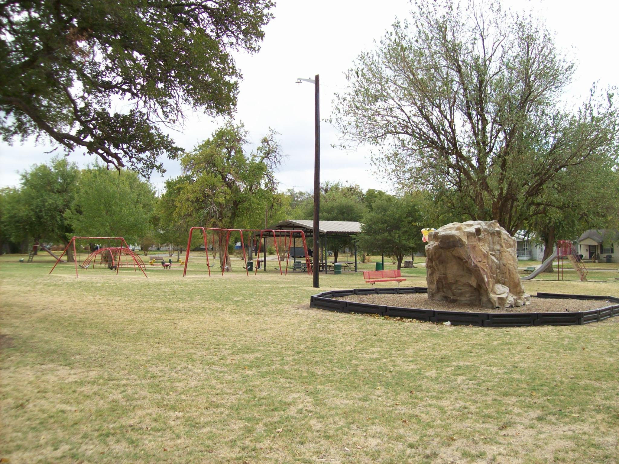 Park with benches, playground equipment, and a shelter.